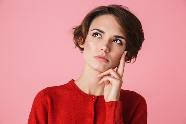 Portret zamyślony piękna młoda kobieta ubrana w czerwone ubrania stojącej na białym tle na różowym tle