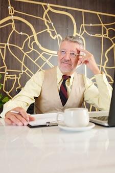 Portret zamyślony starszy przedsiębiorca siedzi przy kawiarnianym stoliku i pracuje nad biznesplanem