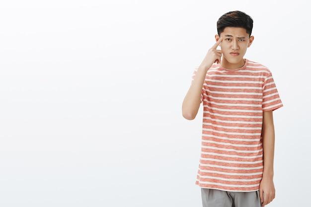 Portret zaniepokojonego i niezadowolonego słodkiego studenta azjatyckiego mężczyzny toczącego palcem wskazującym w pobliżu świątyni pochylonych ramion, reagującego na głupie, głupie działania przyjaciela