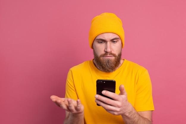 Portret zaniepokojonego, zszokowanego dojrzałego brodatego mężczyzny, sapiącego nieszczęśliwie, trzymającego smartfona, czytającego dziwną i niepokojącą wiadomość na różowo