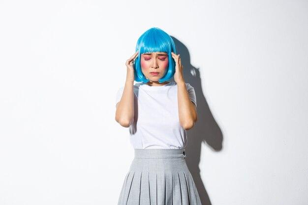 Portret zaniepokojonej młodej azjatki z zamkniętymi oczami i dotykającą głowy, cierpiącej na ból głowy lub migrenę, wystrojona na halloween, stojąca.