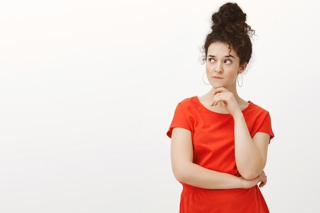Portret zaniepokojonej podejrzliwej kobiety z kręconymi włosami w kokie, patrząc w lewo