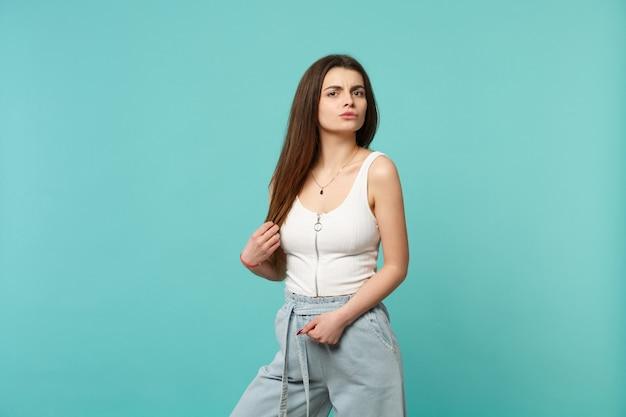 Portret zaniepokojonej zdziwionej młodej kobiety w lekkim ubraniu stojącym, patrząc na kamerę na białym tle na niebieskim turkusowym tle ściany. ludzie szczere emocje, koncepcja stylu życia. makieta miejsca na kopię.