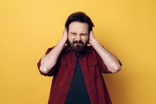 Portret zaniepokojony atrakcyjny mężczyzna zakrywa ucho