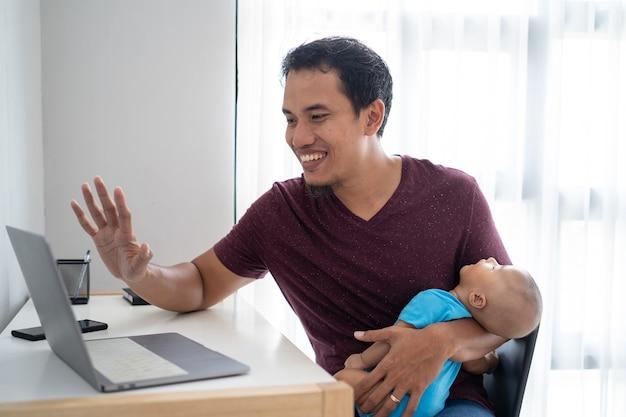 Portret zapracowany ojciec pracujący w domu, trzymając swoje niemowlę dziecko