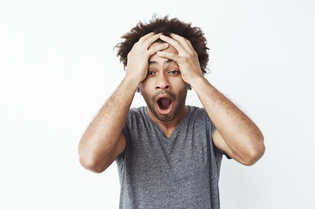Portret zaskoczonego i zszokowanego afrykańskiego mężczyzny z otwartymi ustami dowiadujący się, że przegapił wyprzedaż lub spóźnia się do pracy lub zapomniał odebrać swoje dzieci ze szkoły.