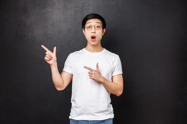 Portret zaskoczonego, zdziwionego młodego azjatyckiego faceta w białej koszuli reaguje z niedowierzaniem i zdziwieniem na coś wyjątkowego i interesującego napisanego po lewej, wskazując podskakując górny róg pod wrażeniem