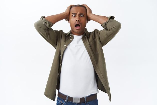 Portret zaskoczonego, zszokowanego i sfrustrowanego, spanikowanego młodego mężczyzny, opadającej szczęki, widzącego coś strasznego