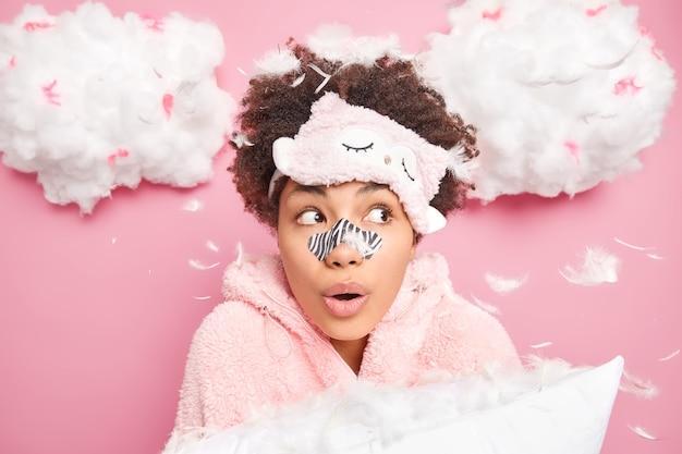 Portret zaskoczonej afroamerykanki wygląda z wielkim zdziwieniem na boku nakłada łatkę na nos, aby zmniejszyć drobne linie, nosi maskę do spania, bielizna nocna trzyma poduszkę budzącą się rano odizolowaną na różowej ścianie