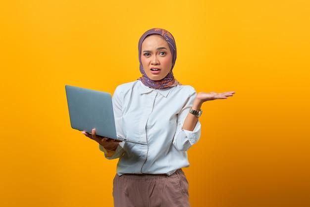 Portret zaskoczonej azjatki trzymającej laptopa ze zdezorientowaną twarzą na żółtym tle