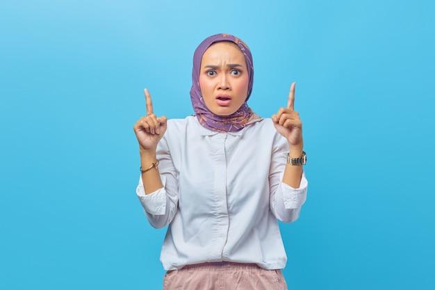 Portret zaskoczonej azjatki wskazującej palce w górę na niebieskim tle