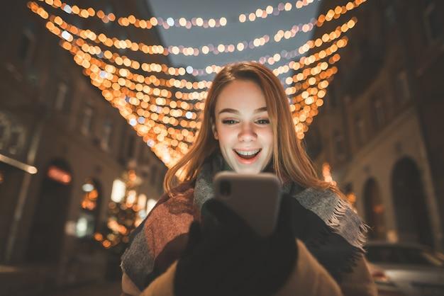 Portret zaskoczonej dziewczyny patrzy na ekran smartfona i uśmiecha się, tło nocnych świateł ulicznych