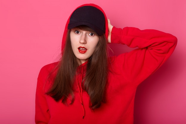 Portret zaskoczonej europejskiej brunetki trzyma rękę na głowie, stoi z otwartymi ustami, ubrany w stylową czerwoną bluzę z kapturem i czarną czapkę, pozuje na różowej ścianie studia.