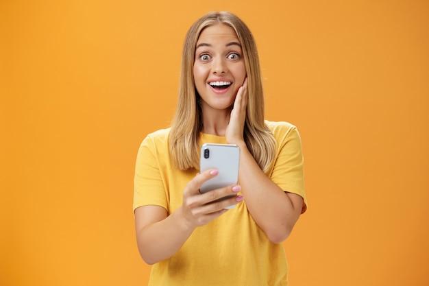 Portret zaskoczonej i pod wrażeniem kobiety reagującej na niesamowitą aplikację w smartfonie dotykającej policzka ze zdumienia i radości, uśmiechającej się szeroko, trzymającej telefon w dłoni nad pomarańczową ścianą