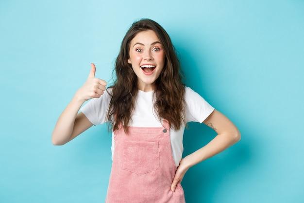 Portret zaskoczonej i podekscytowanej brunetki pokazującej kciuk w górę i mówiącej tak, dyszącej zafascynowanej, chwalącej świetną robotę, stojącej na niebieskim tle.