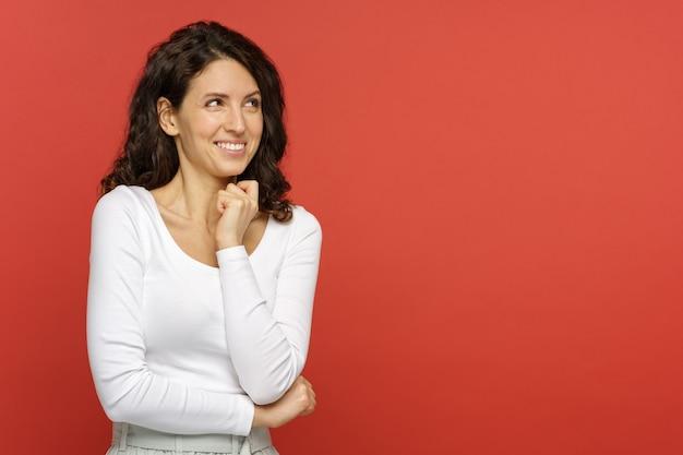 Portret zaskoczonej kobiety z otwartymi ustami i ręką na podbródku, patrząc na puste miejsce na reklamę. podekscytowana pozytywna młoda kobieta zaskoczona niską ceną i rabatem na czerwonym tle studia studio