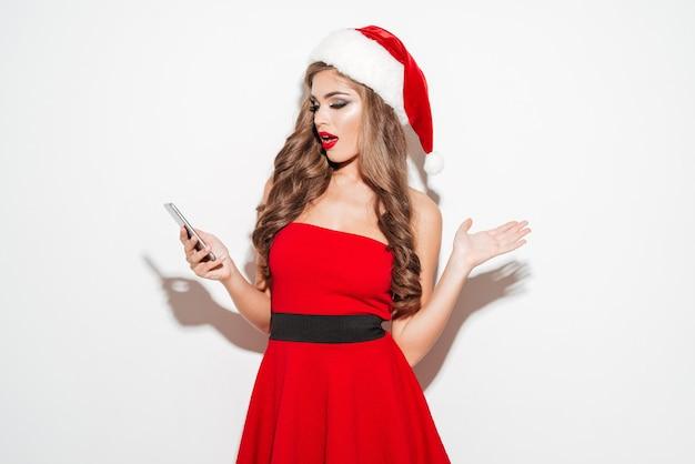 Portret zaskoczonej młodej brunetki w czerwonym stroju świątecznym, patrząc na telefon komórkowy na białym tle