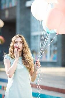 Portret zaskoczonej pięknej kobiety z latającymi wielokolorowymi balonami w mieście