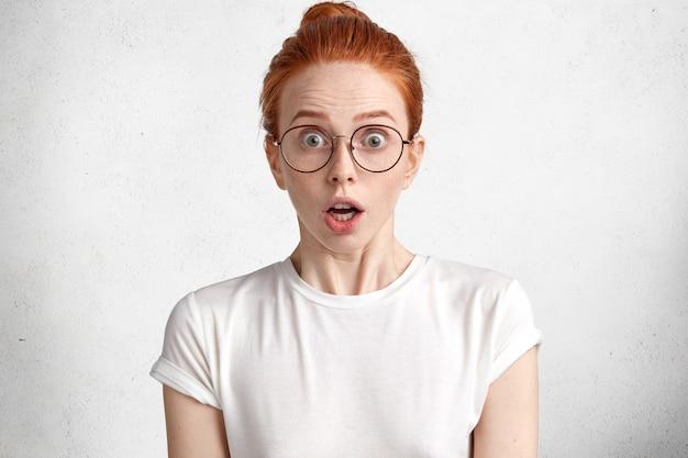 Portret zaskoczonej rudej uczennicy w białej koszulce i dużych okrągłych okularach ma termin na zaliczenie pracy dyplomowej