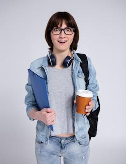 Portret zaskoczonej studentki w okularach z plecakiem, teczką i filiżanką kawy na szarym tle