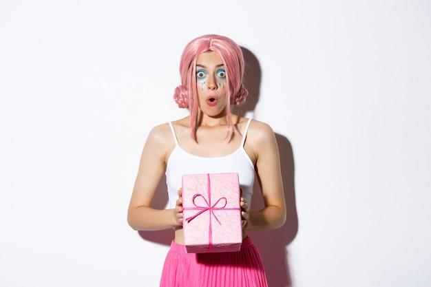 Portret zaskoczony, atrakcyjna dziewczyna wyglądająca podekscytowana, odbiera prezent na urodziny, ubrana w różową perukę, stojąca.