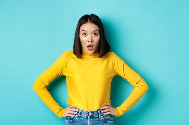 Portret zaskoczony azjatka opuszcza szczękę, słuchając wielkich wiadomości, patrząc zdziwiony na aparat, stojąc w żółtym swetrze na niebieskim tle
