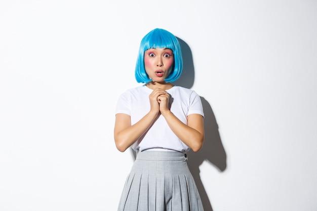 Portret zaskoczony azjatka w niebieskiej krótkiej peruce dysząc zdumiony, słyszy coś szokującego, stojącego w kostiumie na halloween.