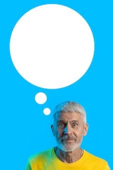 Portret zaskoczony i ciekawy siwy mężczyzna z brodą na niebiesko