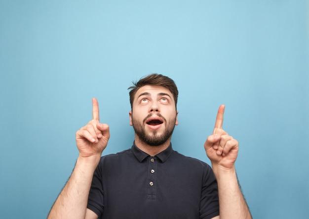 Portret zaskoczony mężczyzna na niebiesko, patrząc w górę i pokazując palce na pustym miejscu
