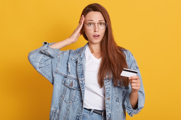 Portret zaskoczony młoda kobieta nosi ubrania casual trzyma usta otwarte i wprowadzenie dłoni w świątyni, trzymając w ręku kartę kredytową