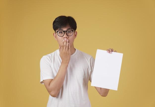 Portret zaskoczony młody człowiek azjatycki ubrany niedbale pokazuje pusty papier pusty afisz na białym tle.