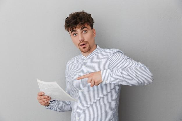 Portret zaskoczony, młody mężczyzna ubrany w koszulę, zastanawiając się, trzymając i czytając gazetę lub magazyn na białym tle nad szarą ścianą