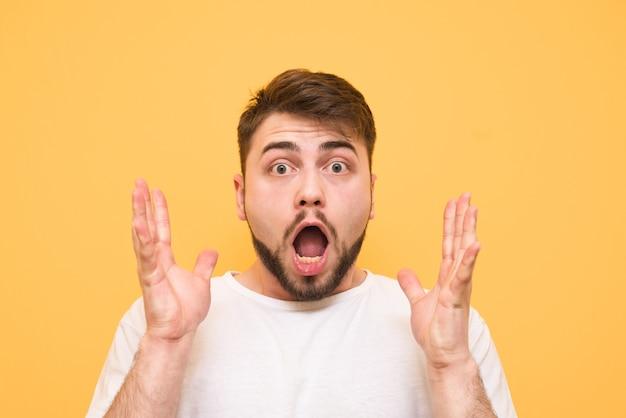 Portret zaskoczony nastolatek na żółtym podnosząc ręce