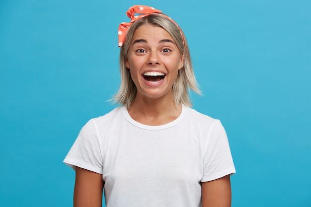 Portret zaskoczony, piękna blondynka młoda kobieta z otwartymi ustami nosi białą koszulkę