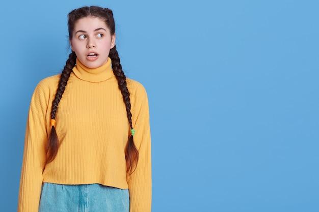 Portret zaskoczony podekscytowana dziewczyna o ciemnych włosach i warkoczykach