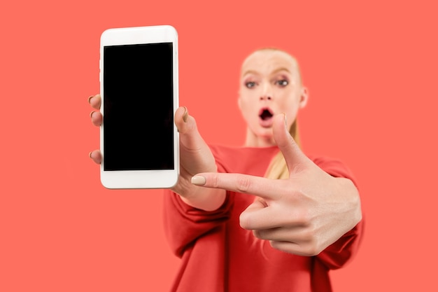 Portret zaskoczony, uśmiechnięty, szczęśliwy, zdziwiony dziewczyna pokazując pusty ekran telefonu komórkowego na białym tle nad koralowym tłem.