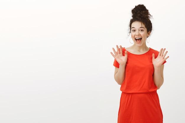 Portret zaskoczony, zachwycony piękną kobietą z kręconymi włosami w dorywczo czerwoną sukienkę