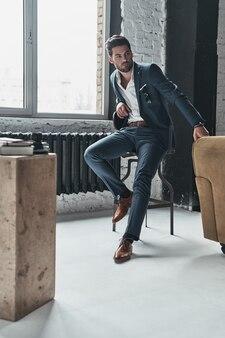 Portret zaufania. pełna długość zamyślonego młodego mężczyzny w pełnym garniturze, odwracającego wzrok, siedzącego na stołku