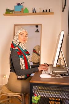 Portret zawoalowanej młodej kobiety na komputerze w domu, pracującej w domu
