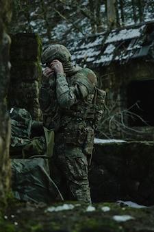Portret zawodnika airsoft w profesjonalnym sprzęcie z karabinem maszynowym w lesie. żołnierz z bronią na wojnie