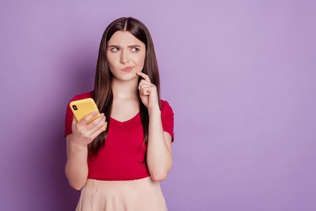 Portret zazdrosnej zazdrosnej pani trzyma telefon wygląda na pustej przestrzeni myśl na fioletowym tle