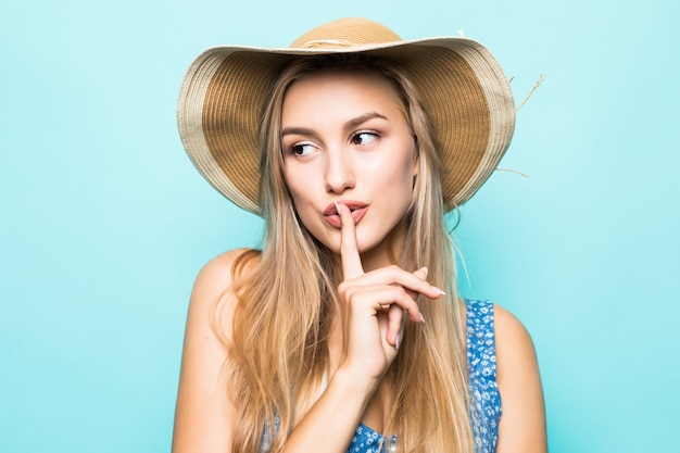 Portret zbliżenie europejskiej uroczej kobiety w dużym słomkowym kapeluszu pokazując palec na ustach, aby zachować tajemnicę na białym tle na niebieskim tle