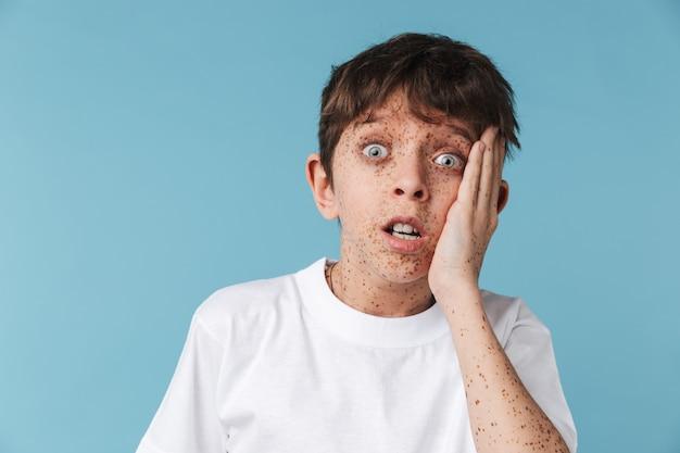 Portret zbliżenie przestraszony młody chłopak z piegami na sobie biały t-shirt dorywczo patrząc z przodu na białym tle nad niebieską ścianą