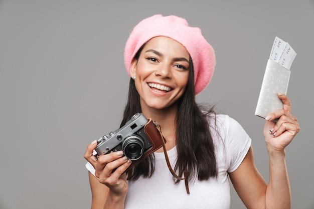 Portret zbliżenie śliczna ładna turystyczna kobieta w berecie, śmiejąc się, trzymając retro aparat i bilety podróżne na białym tle nad szarą ścianą