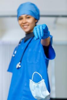 Portret zbliżenie strzał używanej chirurgicznej maski na twarz porzuconej kropli z szczęśliwej, ładnej kobiecej wolności ręka lekarza w niebieskim szpitalnym garniturze ze stetoskopem, uśmiechając się, patrząc na kamerę, podczas gdy pandemiczny koniec pandemii.