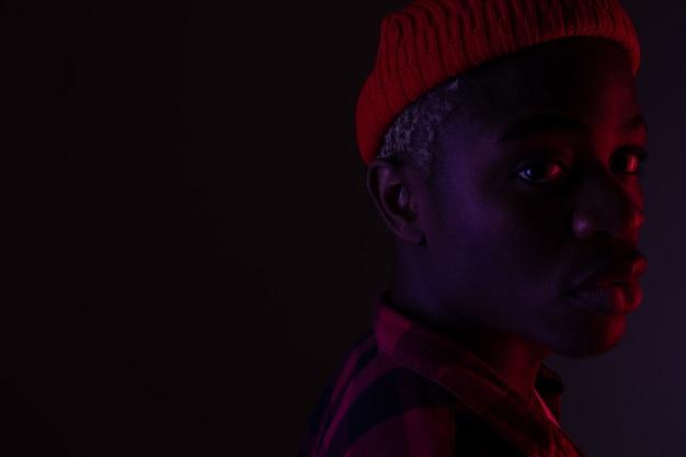 Portret zbliżenie stylowy przystojny czarny człowiek w świetle neonowym w cieniu