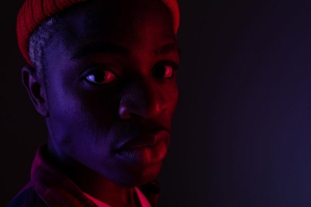 Portret zbliżenie stylowy przystojny murzyn w świetle neonowym