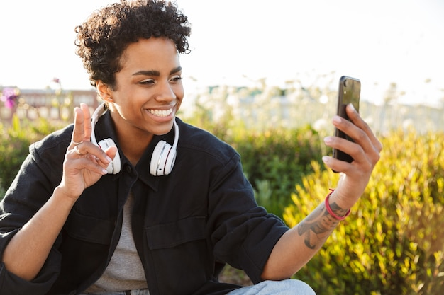 Portret zbliżenie szczęśliwej kobiety ze słuchawkami biorącymi selfie portret na telefonie komórkowym i pokazujący śpiew pokoju siedząc na podłodze