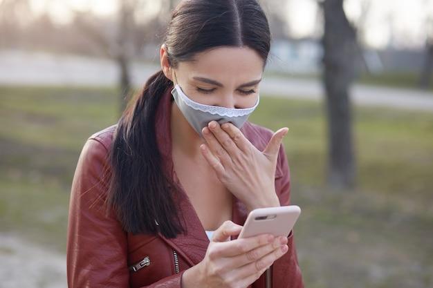 Portret zbliżenie urocza uśmiechnięta brunetka z nowoczesnym smartfonem w rękach, czytaj dobre wieści w sieci społecznościowej o pandemii wirusa koronowego