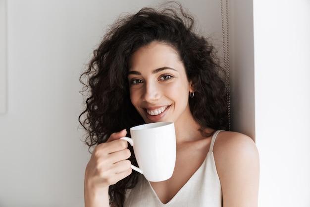 Portret zbliżenie wspaniałej szczęśliwej kobiety z długimi kręconymi włosami, uśmiechając się i pijąc herbatę z filiżanki rano w apartamencie hotelowym